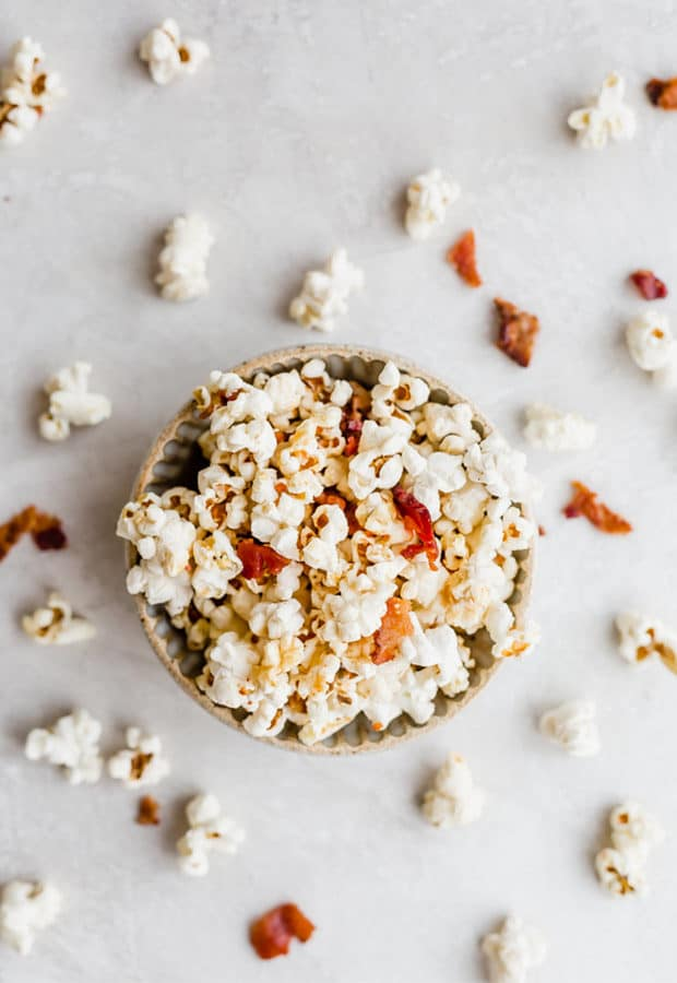 Overhead photo of a bowl of maple bacon popcorn with popcorn kernels scattered around the bowl.
