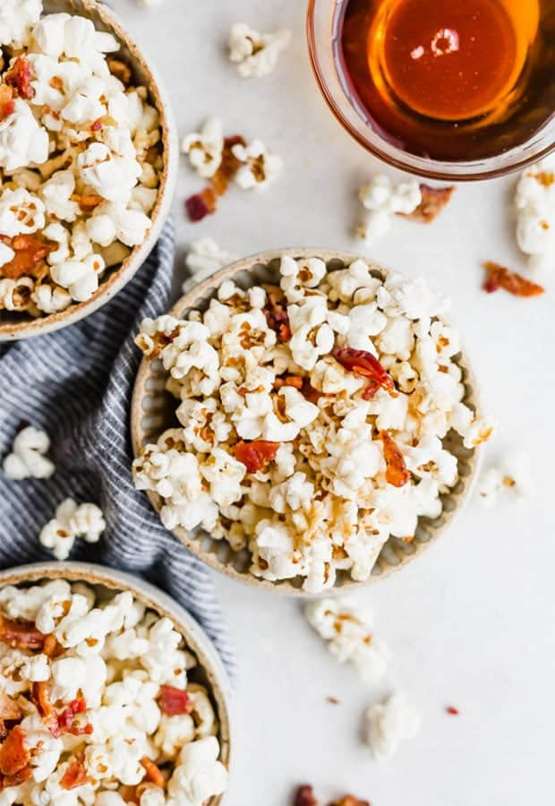 Overhead photo of a bowl of maple bacon popcorn with popcorn kernels scattered around the bowl and a bowl of maple syrup in the top corner.