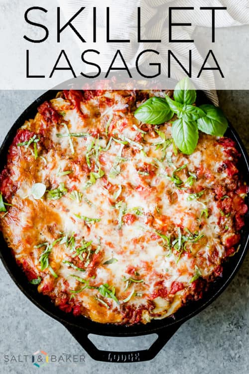 Skillet lasagna in a cast iron pan with fresh basil for garnish.