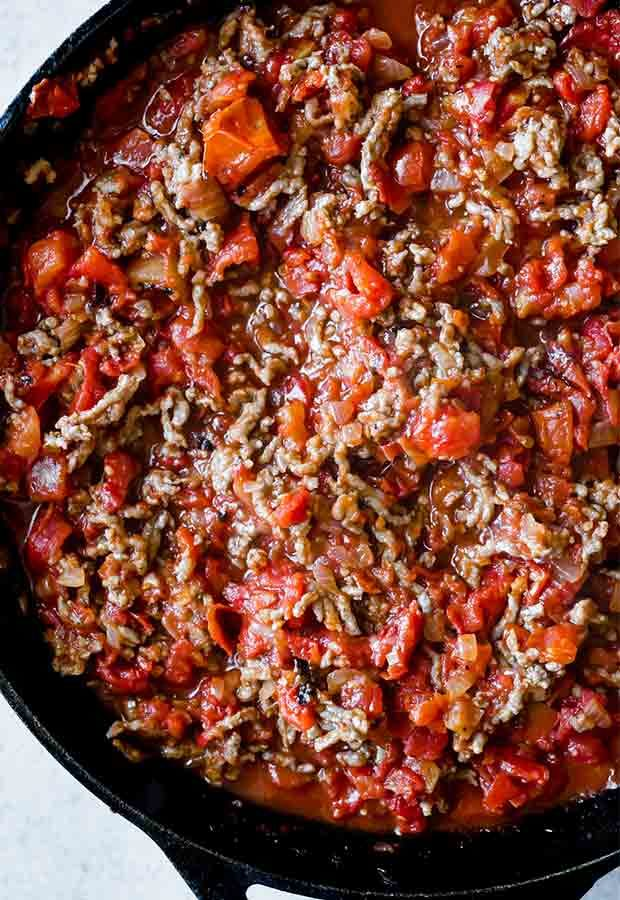 Close up photo of cooked sausage, diced onion, and fire roasted diced tomatoes in a black skillet.