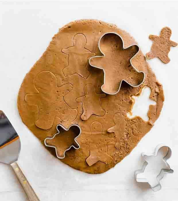 Gingerbread cookie dough rolled out with gingerbread cookie cutters atop the dough.