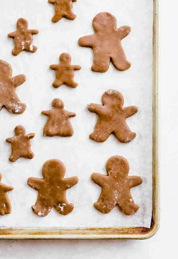 Cut out unbaked gingerbread cookies on a parchment lined baking sheet.