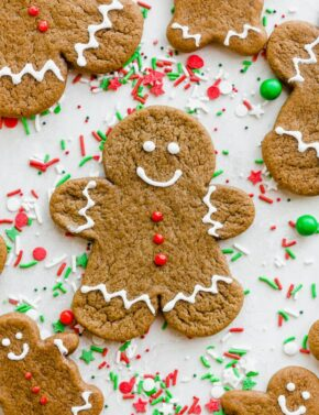 Gingerbread men decorated with white royal icing sitting atop red and green sprinkles.