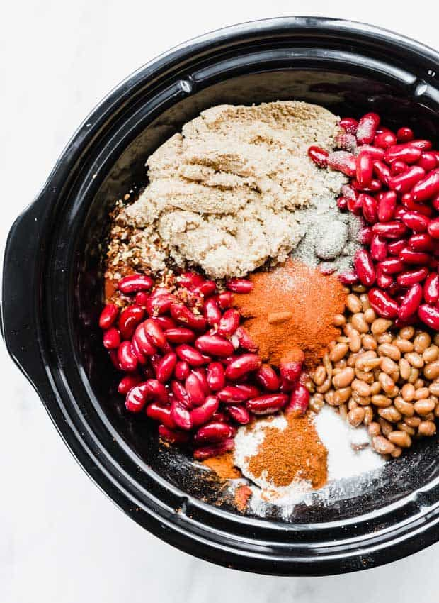 An overhead photo of a black slow cooker full of the ingredients to make sweet and spicy chili.