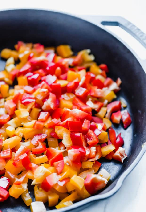 Diced yellow and red peppers in a black skillet in preparation to make sweet and spicy chili.