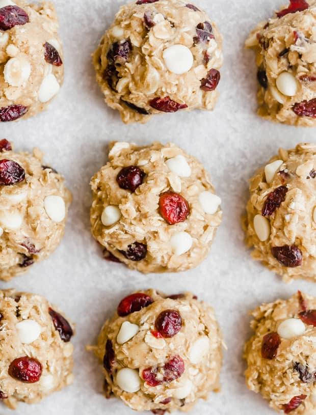 Oatmeal cookie dough balls lined in a row, topped with white chocolate chips and dried cranberries.
