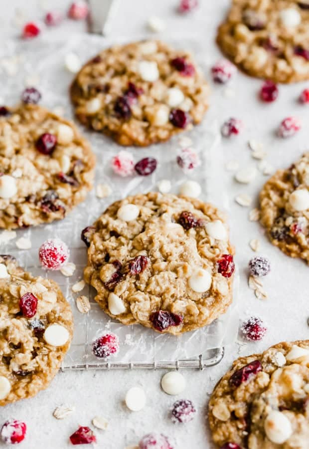 White chocolate cranberry oatmeal cookies scattered on a white background with sugared cranberries surrounding the cookies.