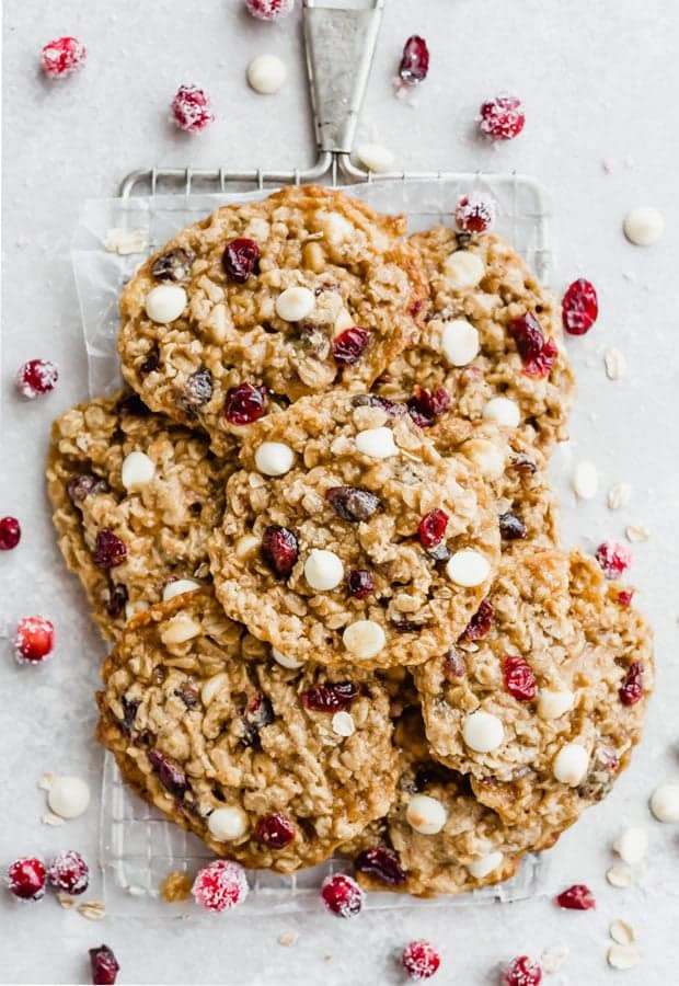 A pile of white chocolate cranberry oatmeal cookies piled on a small cooking rack.