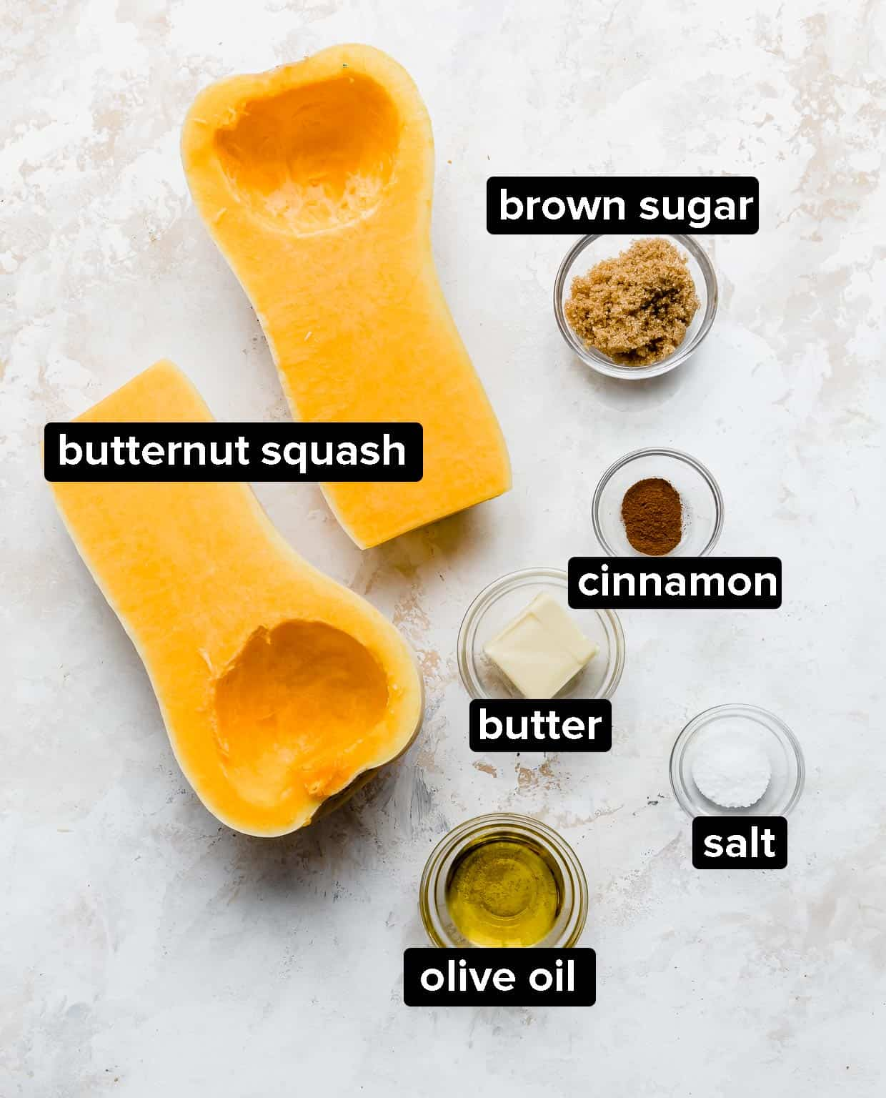 Ingredients used to make cinnamon roasted butternut squash on a white textured background.