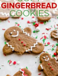 A soft gingerbread cookie man with three red frosting buttons and a bite taken out of the cookies leg.