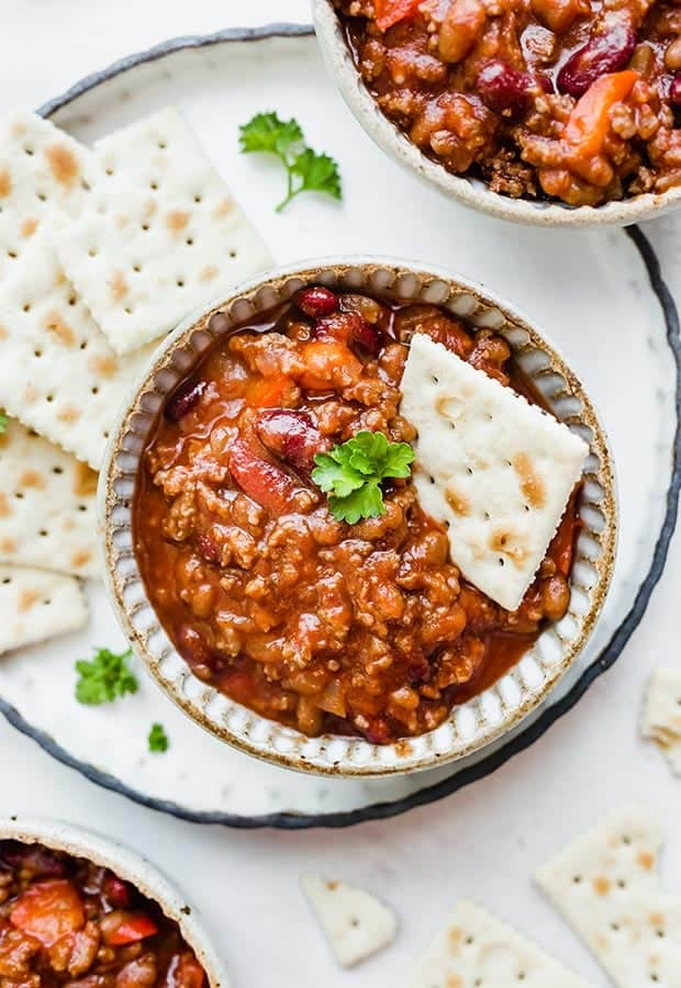 Three bowls of sweet and spicy chili with saltine crackers scattered around the bowls.
