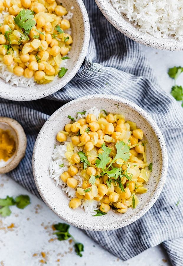 A bowl full of white rice and chickpea curry with a garnish of fresh cilantro.