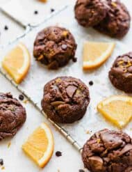 Double chocolate orange cookies surrounded by fresh orange wedges and mini chocolate chips.