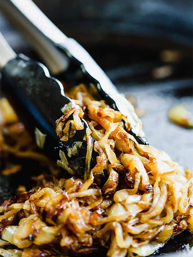 Caramelized onions in a black skillet with tongs grabbing a bunch of the onions.