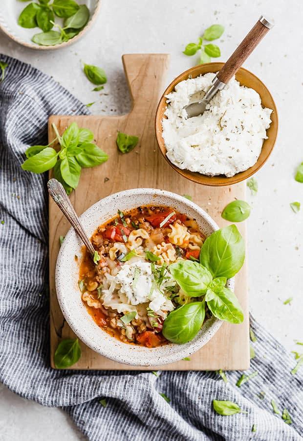 A bowl of lasagna soup topped with fresh basil, ricotta, and mozzarella.