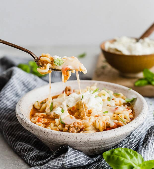 A spoon scooping up lasagna soup with a cheese pull of mozzarella cheese.