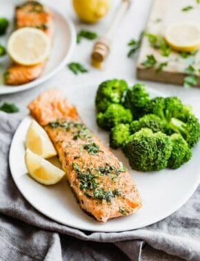 A cooked fillet of salmon topped with a lemon honey glaze, with a serving of broccoli alongside the salmon.