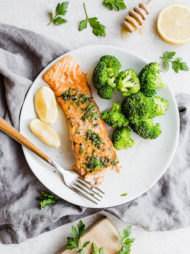 Overhead photo of a salmon fillet on a plate with a fork along side the salmon and a serving of broccoli.
