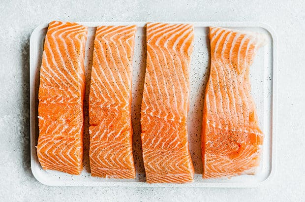 Four salmon fillets a top a white cutting board garnished with salt and black pepper.