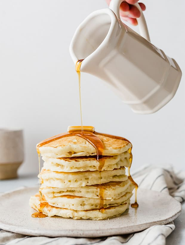 A stack of pancakes on a plate with maple syrup being drizzled overtop.