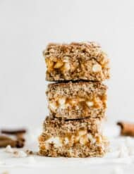Three cinnamon sugar caramelitas stacked on top of each other, with two cinnamon sticks in the background.