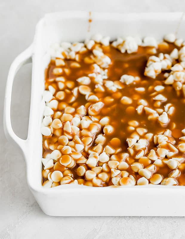 A close up photo of white chocolate chips in a 9 inch square pan, topped with caramel sauce.