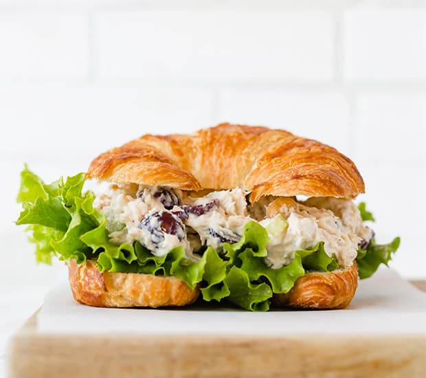 A croissant roll with chicken salad sandwich between the bread.