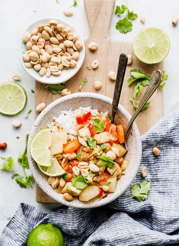 A bowl full of white rice and Massaman curry set on a wooden cutting board with cilantro, limes, and peanuts scattered around the board.