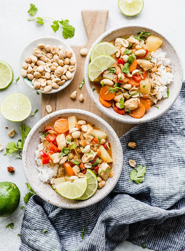 An overhead view of two bowls full of white rice and Massaman curry with lime wedges, cilantro, and peanuts for garnish.