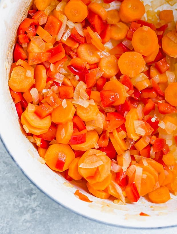 Close up photo of cooked onions, red pepper, and sliced carrots in a dutch oven in preparation to making Massaman curry.