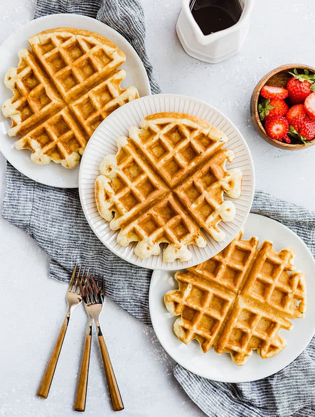 Three waffles on separate plates, with syrup in a white jar and a bowl of strawberries off to the side.