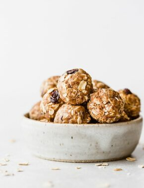 Oatmeal raisin energy bites stacked inside a small ceramic bowl.