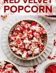 A bowl in the center of the photo full of red velvet popcorn with red velvet cake crumbs surrounding the bowl.