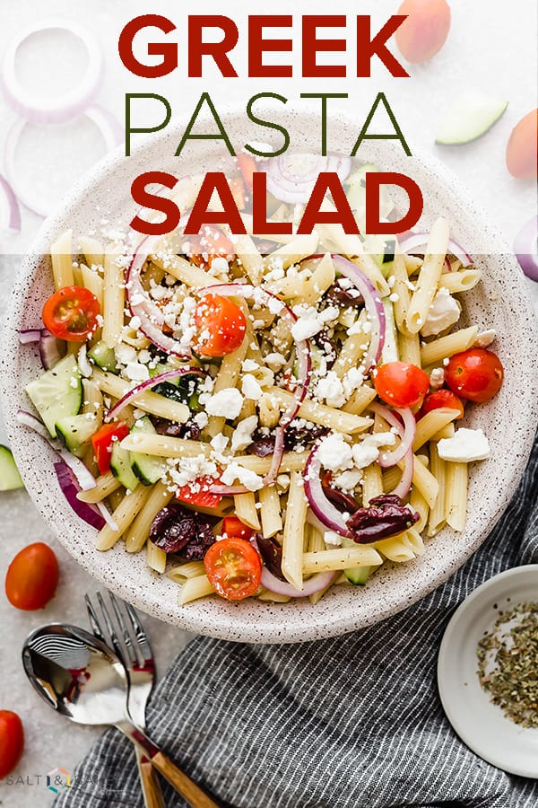 An overhead photo of a large bowl with cooked pasta, tomatoes, red onion, feta cheese, and cucumber, ultimately making the best greek pasta salad.