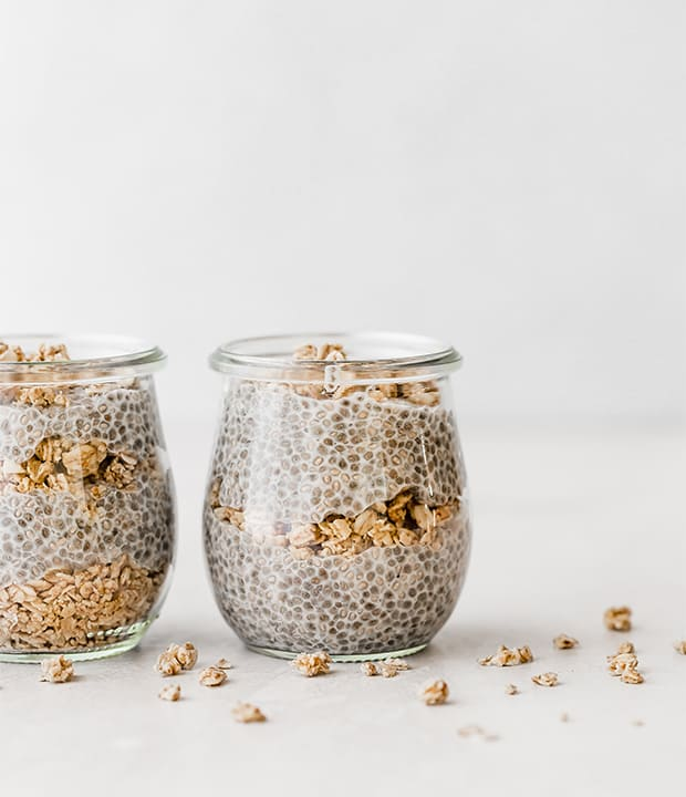 Two small glass jars with layers of granola and chia pudding.