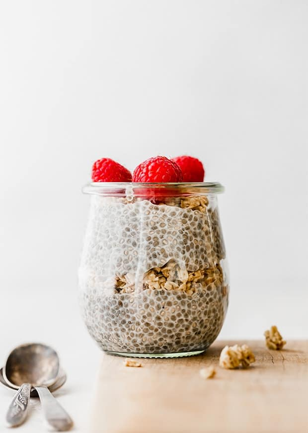 Glass jar full of chia pudding with a layer of granola in the middle and topped with fresh raspberries.