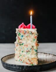 A slice of Funfetti Cake with one candle lit on the top of the cake slice.