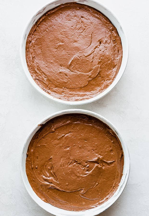 Overhead photo of two circular cake pans filled with German chocolate cake batter.