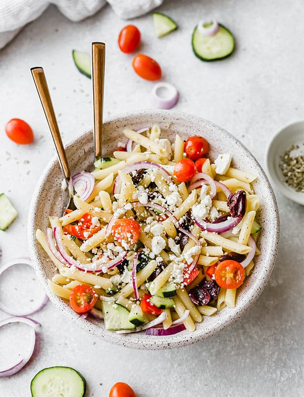 A large bowl with a two forks in the bowl of cooked pasta, tomatoes, red onion, feta cheese, and cucumber, ultimately making the best greek pasta salad.
