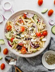 A large bowl with cooked pasta, tomatoes, red onion, feta cheese, and cucumber, ultimately making the best greek pasta salad.