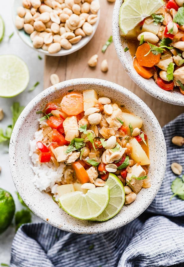 A bowl of Massaman curry with cilantro and lime wedges for garnish.
