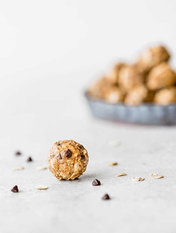 A no-bake energy bite in the foreground of the photo, with a stack of energy bites in the background.