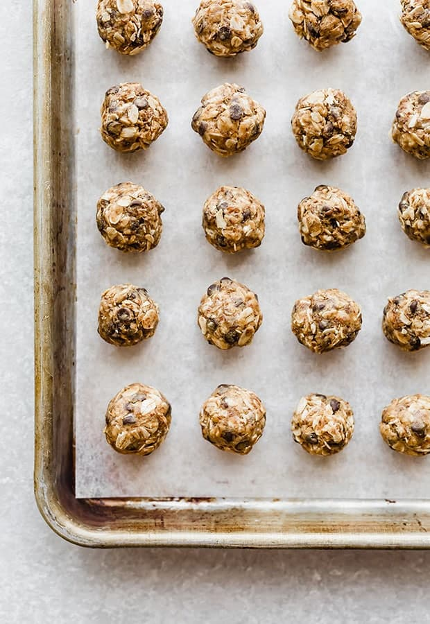 Small no-bake energy bites on a baking sheet lined with parchment paper.