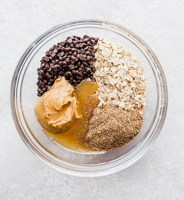 A glass bowl with oats, chocolate chips, peanut butter, flax seed, honey, and vanilla; prepping to make no-bake energy bites.