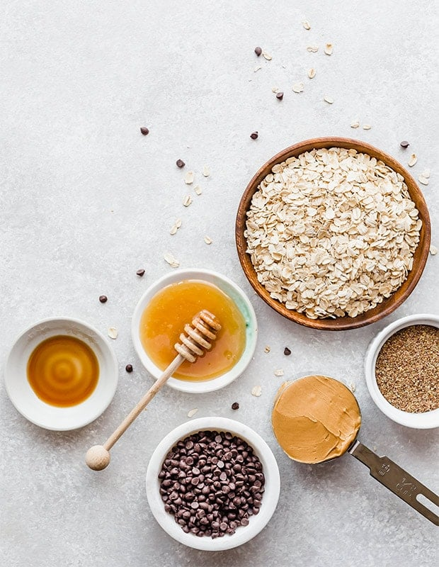 Overhead view of the ingredients needed to make no-bake energy bites; honey, oats, flax seed, peanut butter, chocolate chips, and vanilla.