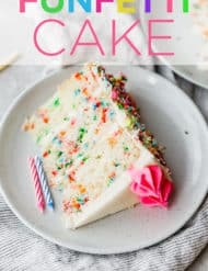 A slice of a layered Funfetti Cake, with birthday candles scattered around the cake slice.