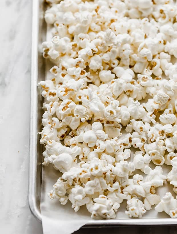 A baking sheet lined with wax paper and covered in popped popcorn.