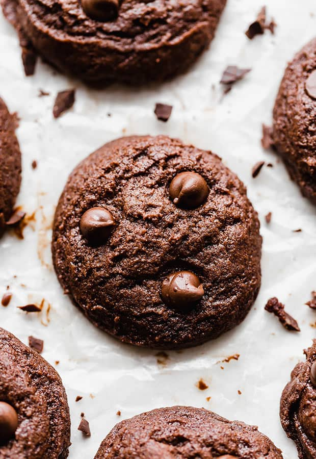 A close up photo of a brownie cookie surrounded by chopped chocolate.
