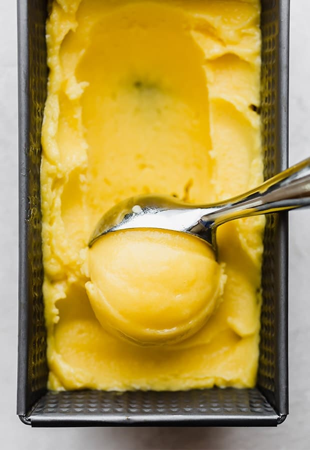 A scoop of creamy mango sorbet being scooped.