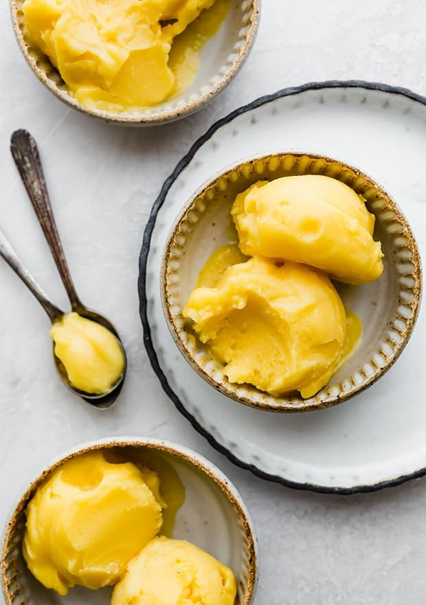 Two scoops of mango sorbet in a small bowl.